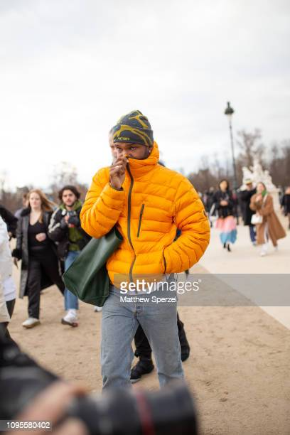 Frank Ocean is seen attending Louis Vuitton during Men's Paris Fashion Week AW19 wearing yellow down jacket with green beanie and blue jeans on...