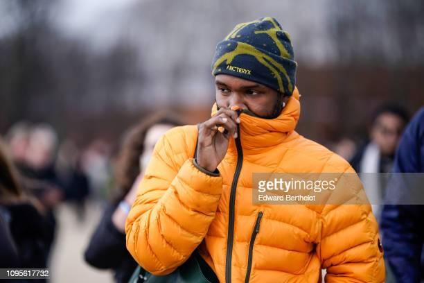 Frank Ocean wears an orange puffer jacket, a beanie hat from Arc'Teryx, outside Louis Vuitton, during Paris Fashion Week - Menswear F/W 2019-2020, on...