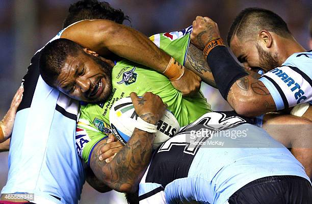 Frank Paul Nuuausala of the Raiders is tackled by Tinirau Arona Andrew Fifita and Wade Graham of the Sharks during the round one NRL match between...