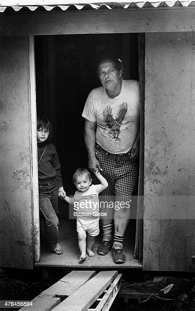 Frank Perkins partially disabled and unable to work poses with two of his three children Perkins and his wife have fashioned a makeshift home on the...