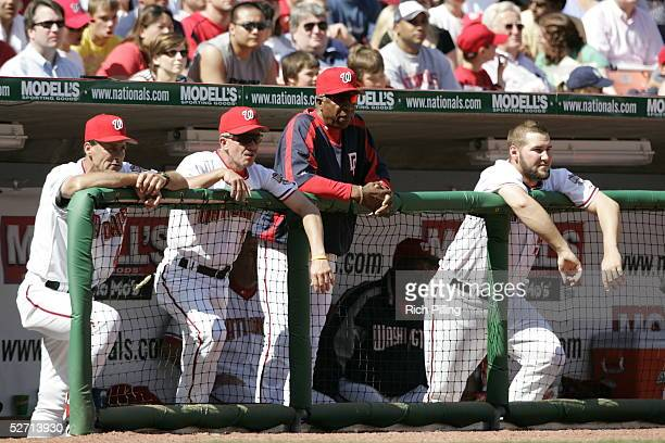 Frank Robinson of the Washington Nationals watches from the dugout with bench coach Eddie Rodriguez Randy St Clair and TJ Tucker during the game...