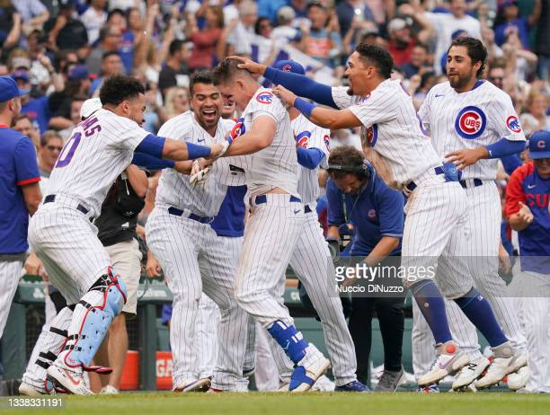 Frank Schwindel of the Chicago Cubs is mobbed by teammates following his walk off single during the ninth inning of a game against the Pittsburgh...