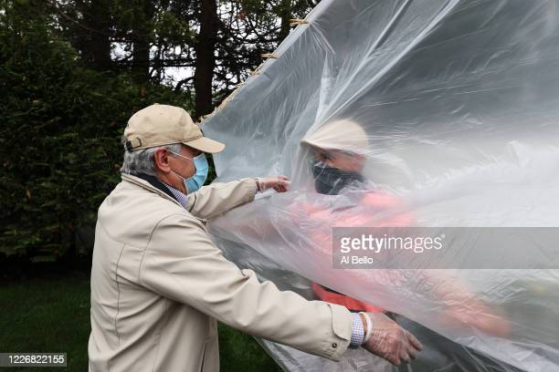 Frank Sileo hugs his father Domenik Sileo through a plastic drop cloth hung up on a homemade clothes line during Memorial Day Weekend on May 24 2020...