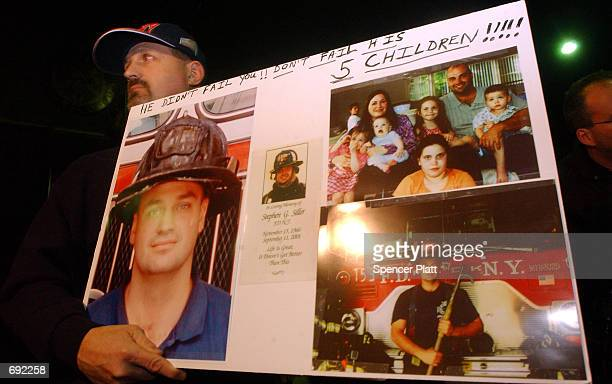 Frank Siller holds pictures of his late brother New York City fire fighter Stephen Siller at a rally for victims of the September 11 attacks on the...