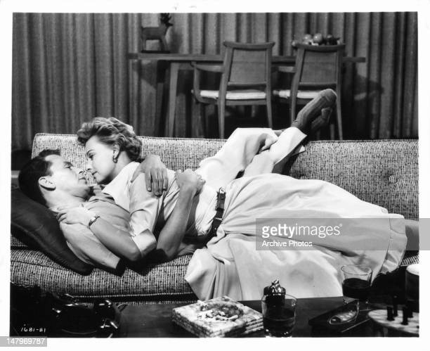 Frank Sinatra and Lola Albright laying on the couch together in a scene from the film 'The Tender Trap' 1955