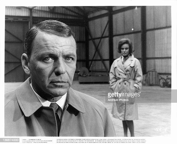 Frank Sinatra and Nadia Gray standing in warehouse in a scene from the film 'The Naked Runner' 1967