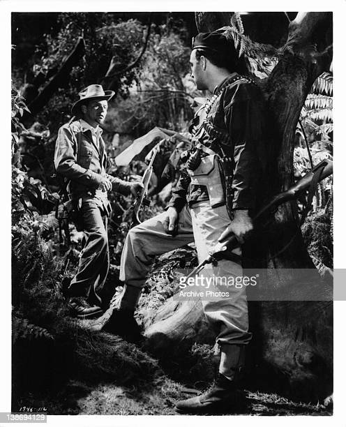 Frank Sinatra and Richard Johnson portray leaders of a United States Army guerilla band in tense exciting Burma jungle battle scenes from the film...