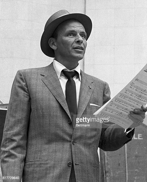 Frank Sinatra hold sheet music during a recording session