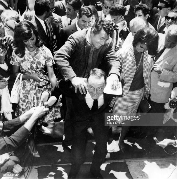 Frank Sinatra is assisted by Dean Martin at a handprint ceremony outside Grauman's Chinese Theatre Hollywood 20th July 1965 With them are Sinatra's...
