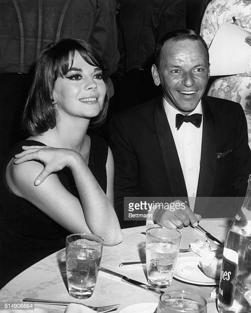 "Frank Sinatra, now a film star and producer as well, greets Natalie Wood, with whom he worked hard to arrange the premiere of ""My Fair Lady,"" at..."
