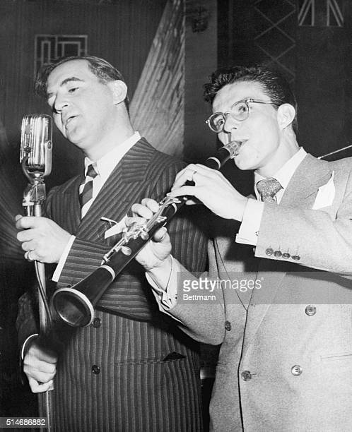 Frank Sinatra plays Benny Goodman's clarinet and wears his glasses while Goodman steps up to the microphone and sings