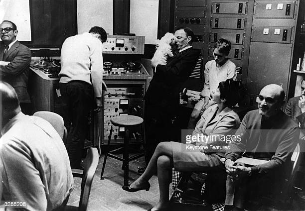 Frank Sinatra relaxes with Mia Farrow's white dog Fluffy during a break in a recording session with his daughter Nancy