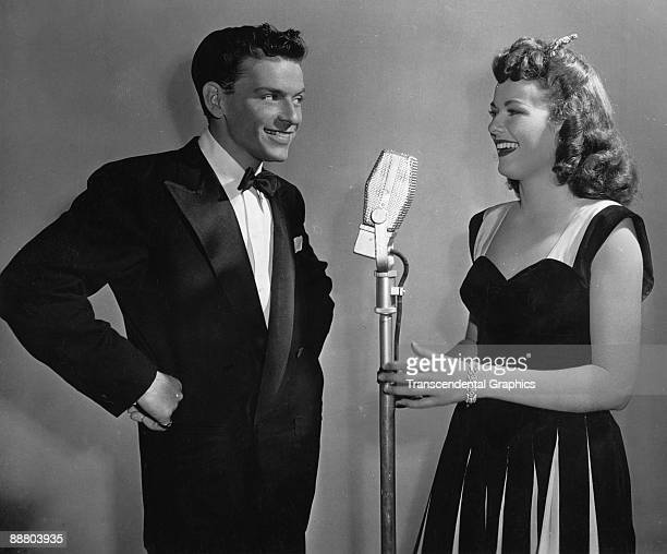 Frank Sinatra speaks with Barbara Hale at the microphone during a radio broadcast around 1940 in New York