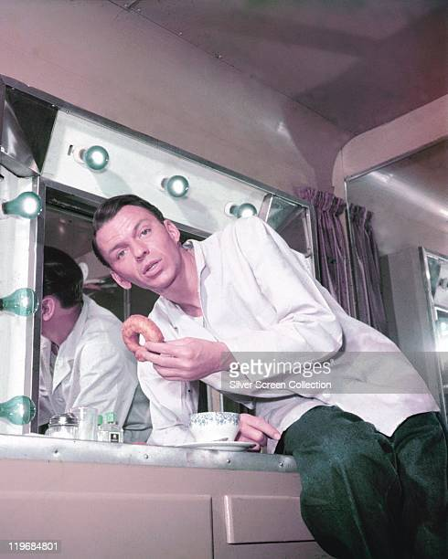 Frank Sinatra , US singer and actor, enjoying a doughnut in his trailer, with a mirror surrounded with lightbulbs behind him, circa 1955.
