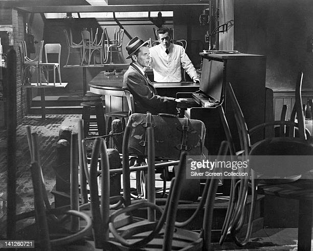 Frank Sinatra US singer and actor sitting at a piano in an empty bar with the chairs on the tables with Cliff Ferre behind the bar in a publicity...