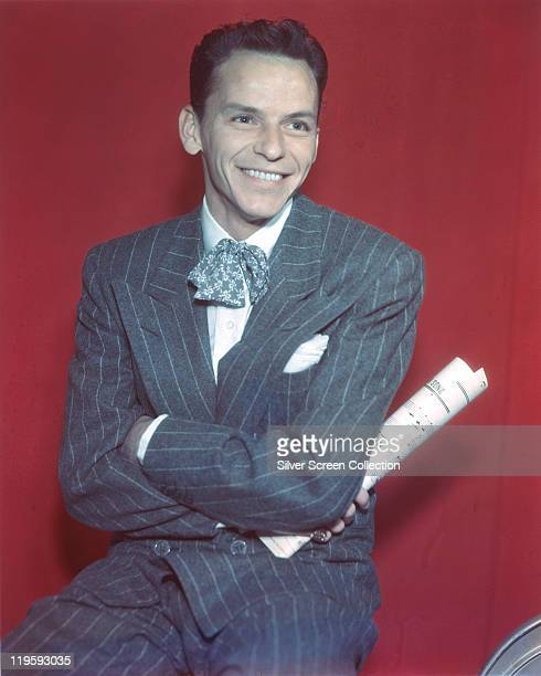 Frank Sinatra US singer and actor smiling wearing a grey pinstriped suit in a studio portrait against a red background circa 1950