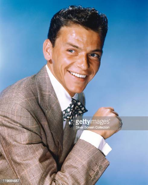 Frank Sinatra US singer and actor smiling while dressed in a grey jacket a white shirt and a blueandwhite bow tie in a studio portrait against a...