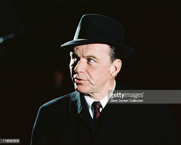 Frank Sinatra US singer and actor wearing a black hat and black overcoat against a black background circa 1970