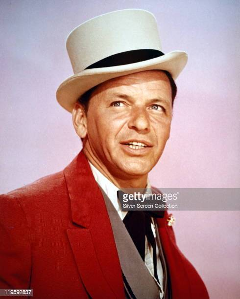 Frank Sinatra US singer and actor wearing a white top hat with a black band white shirt grey wasitcoat red jacket and a black western tie in a studio...