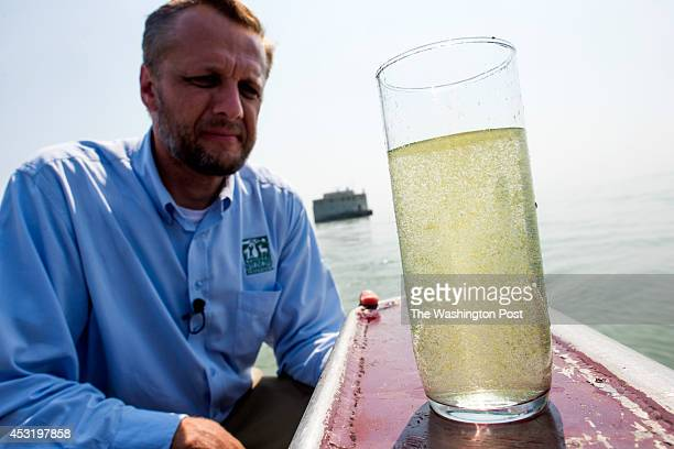 Frank Szollisi manager of the Great Lakes Outreach for the National Wildlife Federation looks at a glass filled with water out of Lake Erie a few...