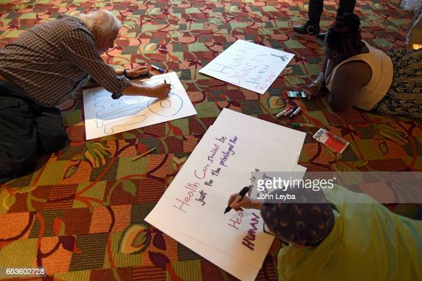 Frank Tapy Together Colorado Ashlee Taylor with Shorter AME and Rabi Evette Lutman bottom work on signs before the press conference Shorter Community...