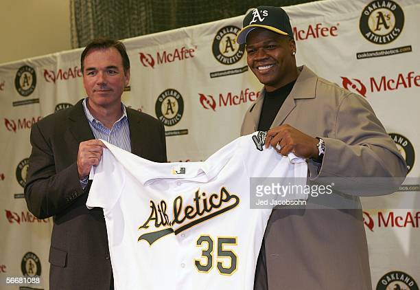 Frank Thomas and general manager Billy Beane of the Oakland Athletics hold Thomas's new jersey at a press conference after he signed a oneyear...