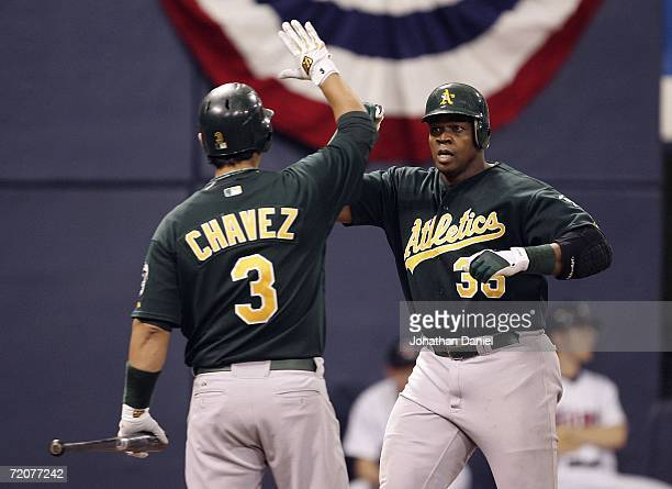 Frank Thomas of the Oakland Athletics is congratulated by teammate Eric Chavez after hitting his second home run of the game, a solo shot in the 9th...