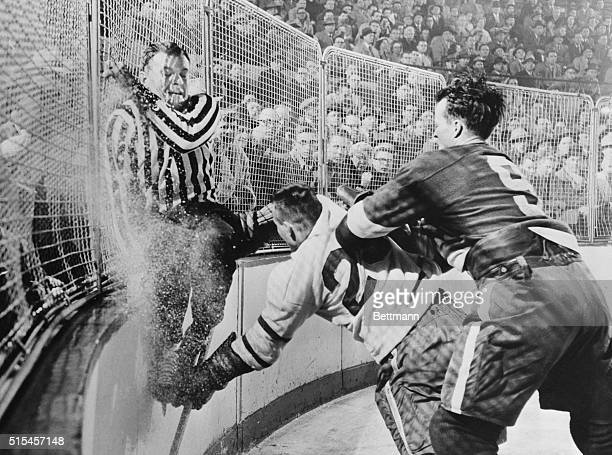 Frank Udvari, tries to get out of harm's way as Red Wing Gordie Howe sends Toronto's Gordie Hannigan into the boards during semifinal Stanley Cup...