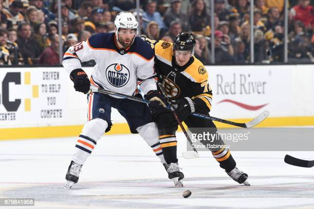 Frank Vatrano of the Boston Bruins fights for the puck against Patrick Maroon of the Edmonton Oilers at the TD Garden on November 26 2017 in Boston...