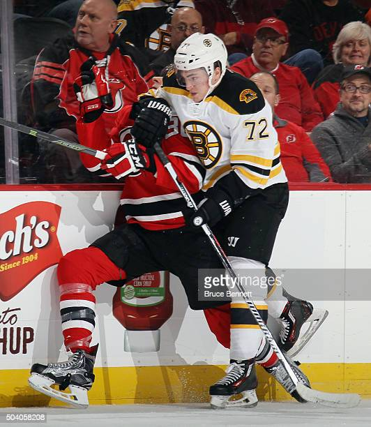 Frank Vatrano of the Boston Bruins hits Jim O'Brien of the New Jersey Devils during the first period at the Prudential Center on January 8 2016 in...