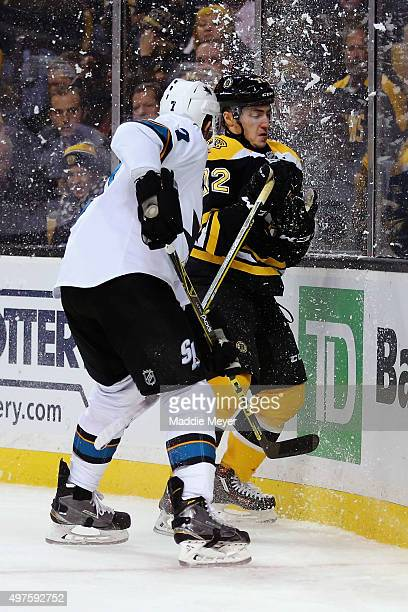 Frank Vatrano of the Boston Bruins is checked into the boards by Paul Martin of the San Jose Sharks during the third period at TD Garden on November...