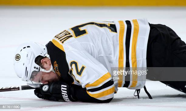 Frank Vatrano of the Boston Bruins is on the ice after he is hit with a high stick from Brian Boyle of the New Jersey Devils in the second period on...