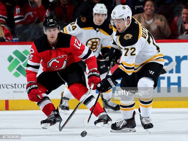 Frank Vatrano of the Boston Bruins takes the puck as Ben Lovejoy of the New Jersey Devils defends on November 22 2017 at Prudential Center in Newark...