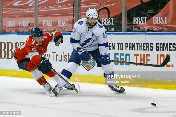 Frank Vatrano of the Florida Panthers and Alex Killorn of the Tampa Bay Lightning chase a loose puck during first period action at the BB&T Center on...