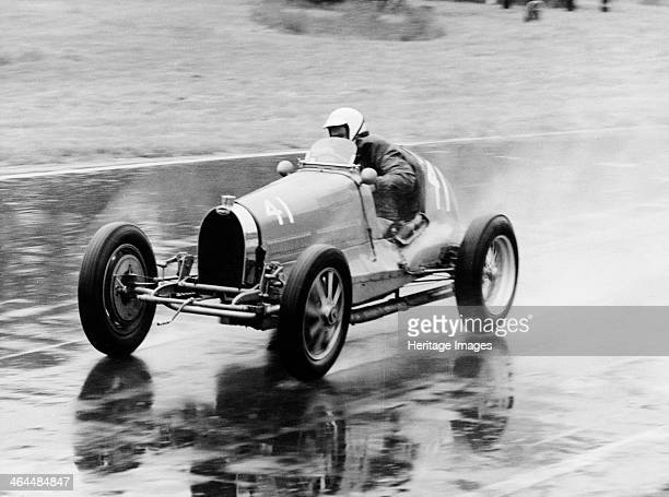 Frank Wall driving a Bugatti Type 35B, 1926. Driving on a wet racetrack, with spray coming off the back wheels.