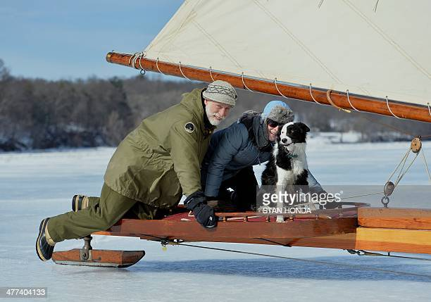 Frank Wall KatieJean Wall and Sancho get on board the ice boat Aurora as they sail on a frozen Hudson River March 7 2014 in Barrytown New York These...