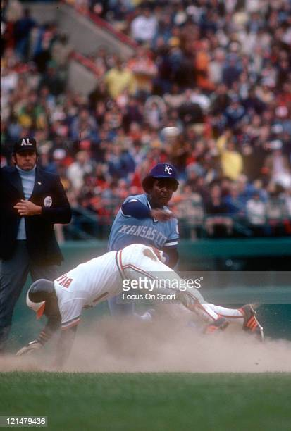 Frank White of the Kansas City Royals gets his throw off to first base avoiding the slide of Al Bumbry of the Baltimore Orioles during an Major...