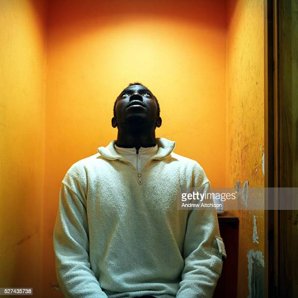 Frank who makes regular long distance call to his family in Ghana in a phone booth of a Long distance call shop Hackney London