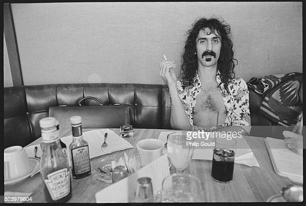 Frank Zappa sits and smokes at a diner table which is littered with various glasses and condiments bottles