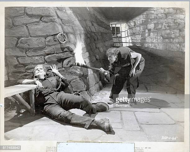 Frankenstein in chains hunchback approaches with fire Undated photo