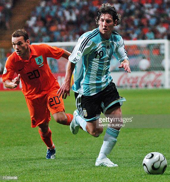 Argentinian forward Lionel Messi runs with the ball in front of Dutch midfielder Wesley Sneijder in the opening round Group C World Cup football...