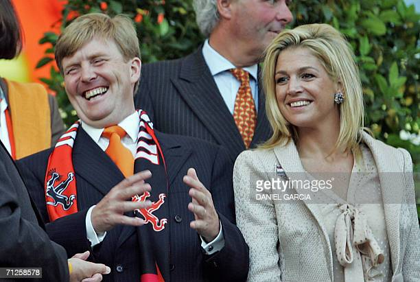 Dutch Crown Prince Willem Alexander laughs next to his wife Princess Maxima as they attend the opening round Group C World Cup football match The...