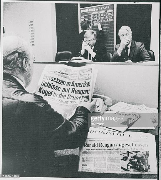 Broker at foreign currency exchange reads newspapers banner lining assassination attempt on President Reagan during midday fixing of the Dollar...