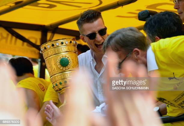 Frankfurt's defender Marco Russ holds the trophy during celebrations after winning the German Cup final in Dortmund western Germany on May 28 2017 /...