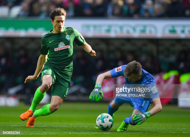 Frankfurt's Finnish goalkeeper Lukas Hradecky and Bremen's Danish midfielder Thomas Delaney vie for the ball during the German first division...