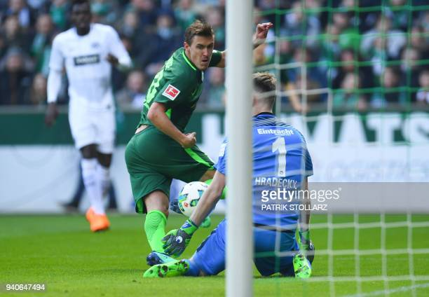 Frankfurt's Finnish goalkeeper Lukas Hradecky and Bremen's German forward Max Kruse vie for the ball during the German first division Bundesliga...