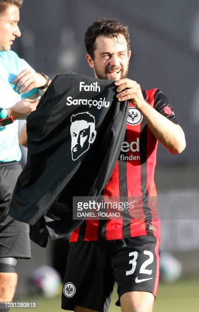 Frankfurt's German midfielder Amin Younes holds a shirt with the name and the portrait of Fatih Saracoglu, a victim of the Hanau racist shooting one...