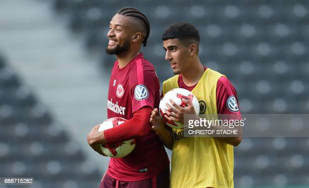 Frankfurt's Jamaican defender Michael Hector and Frankfurt's midfielder Aymen Barkok chat during a training session on the eve of the German Cup...