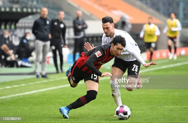 Frankfurt's Japanese midfielder Daichi Kamada and Moenchengladbach's Algerian defender Ramy Bensebaini vie for the ball during the German first...