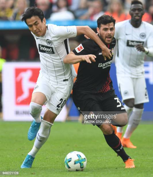 Frankfurt's Japanese midfielder Makoto Hasebe and Leverkusen's German forward Kevin Volland vie for the ball during the German first division...